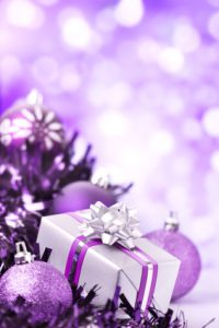 Purple and silver Christmas baubles and a gift in front of defocused purple and white lights.